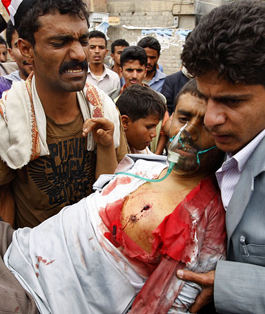 A wounded Yemeni dissident tribesman is carried into a makeshift clinic outside Sanaa University during clashes with government forces on June 1, 2011