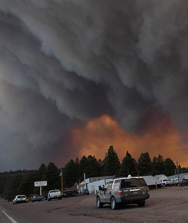 Firefighters worked furiously Monday to save a line of mountain communities in eastern Arizona from a gigantic blaze that has forced thousands of people from their homes and cast a smoky haze over states as far away as Iowa.