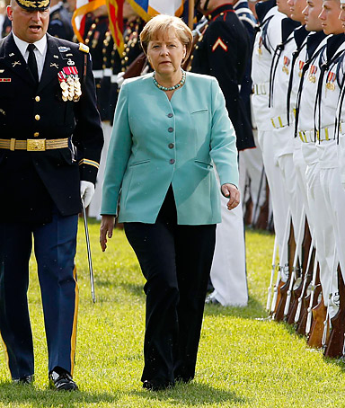 German Chancellor Angela Merkel reviews U.S. military personnel with U.S. President Barack Obama during an official State Arrival ceremony for Merkel on the South Lawn at the White House in Washington June 7, 2011.