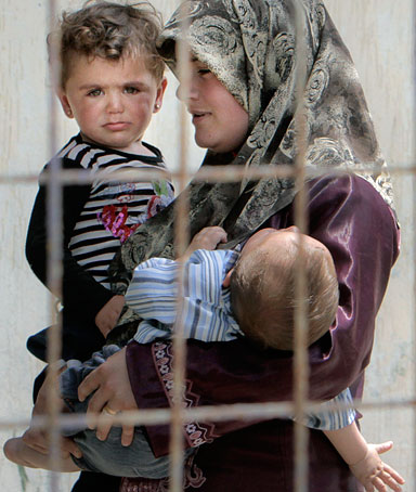 A Syrian refugee woman carries two children in a camp in Yayladagi, Turkey, near the Syrian border, Sunday, June 12, 2011.