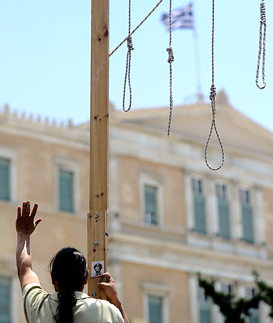 A demonstrator stands on a fake gallows set in front of the Greek parliament on June 28, 2011.