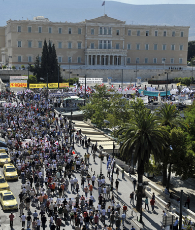 Communist-affiliated unionists rally toward the Greek parliament on June 28, 2011