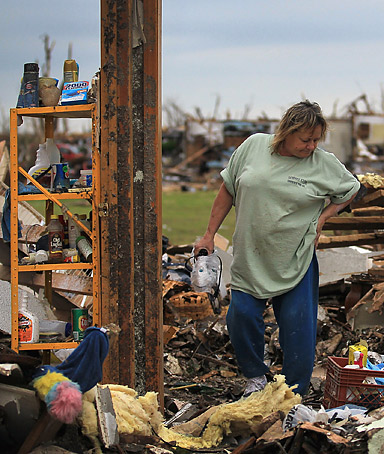 Bee Hicks salvages what she can from her mother-in-laws home the tornado passed through Joplin, Missouri on May 27, 2011.