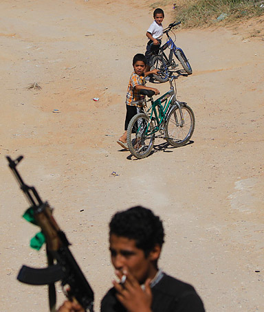Taken on a government-organized tour, a Libyan man stands with his gun as children ride bikes behind him in the village of Assabaa.