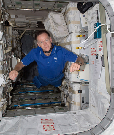 NASA astronaut Chris Ferguson, STS-135 commander poses in the Raffaello multi-purpose logistics module following the completion of the transfer of supplies to and from the two spacecraft on the International Space Station July 17, 2011 in space
