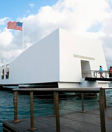 American flag fluttering on a memorial building, USS Arizona Memorial, Pearl Harbor, Honolulu, Oahu, Hawaii Islands, USA.
