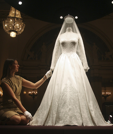 Exhibition curator, Caroline de Guitaut, adjusts the wedding dress of Britain's Catherine, Duchess of Cambridge at Buckingham Palace in London July 20, 2011
