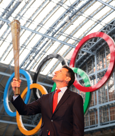 This file picture taken on June 8, 2011 shows Sebastian Coe, Chairman of the London 2012 Olympic Organising Committee, posing for pictures with the newly unveiled 2012 London Olympic Torch, at St Pancras International Rail Station, central London