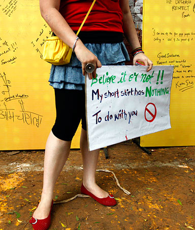 A woman holds a placard as messages written by people are seen in the background at the Delhi