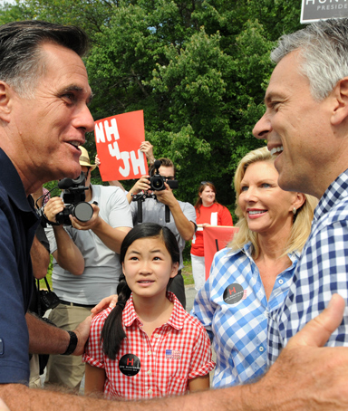 Republican presidential candidates Jon Huntsman (right) and Mitt Romney (left) greet each other prior to marching in a Fourth of July parade