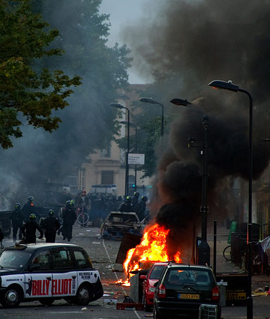 Riot police tackle a mob after a number of cars are set alight in Hackney, north London on August 8, 2011.