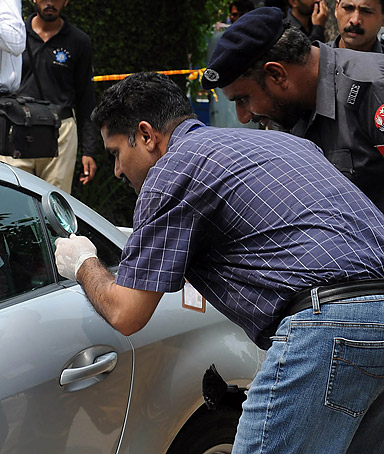 Pakistani police examine the car of the abducted son of former Pakistani governor Salman Taseer in Lahore on August 26, 2011.