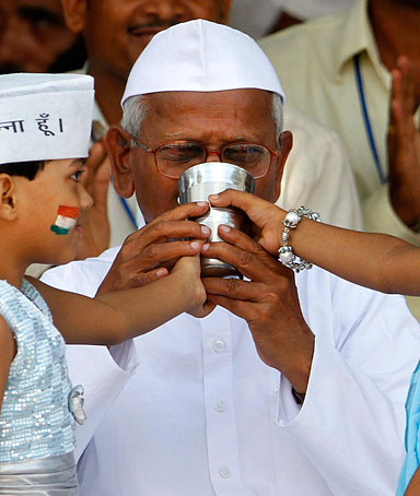 India's anti-corruption activist Anna Hazare drinks coconut water and honey to break his fast in New Delhi, India, Sunday, Aug. 28, 2011.