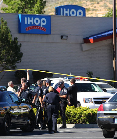 Law enforcement officers and National Guard members in uniform stand at the shooting scene at an IHOP restaurant in Carson City, Nevada September 6, 2011.