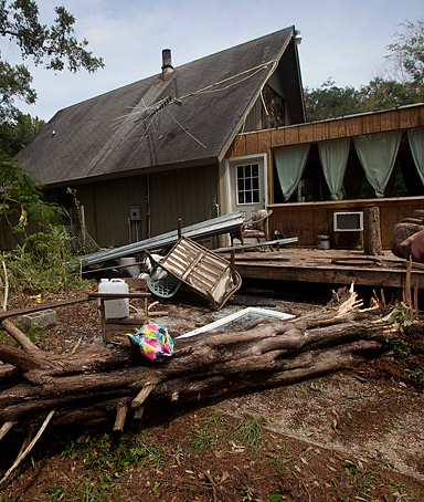 Debris lies around a house in Bayley's Corner, Alabama after strong winds blew down trees and sucked the bed out of the upper bedroom of this home on September 4, 2011.
