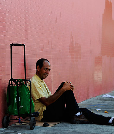 Juan Morena sits on the sidewalk as he waits for the opening of the soup kitchen of St. Francis Center on September 13, 2011 in Los Angeles, California.