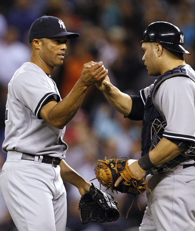 New York Yankees closer Mariano Rivera, left, is greeted by catcher Russell Martin after the team beat the Seattle Mariners in a baseball game Tuesday, Sept. 13, 2011, in Seattle