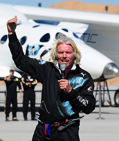 Sir Richard Branson addresses a crowd of guests and media in front of WhiteKnightTwo, with the SpaceShipTwo vessel in the middle, at Spaceport America, on Oct. 17, 2011