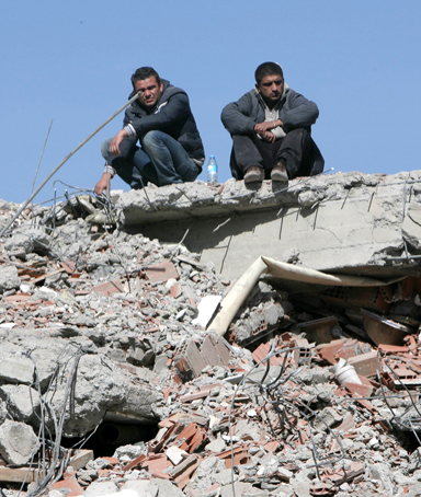Turkish men sit amid the rubble of an earthquake-damaged building on October 24, 2011 in Van, eastern Turkey