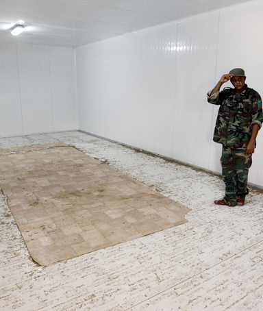 A Libyan revolutionary fighter stands in the empty freezer in a commercial center, where the body of Libyan dictator Moammar Gadhafi was displayed in Misrata, Libya, Tuesday Oct. 25, 2011