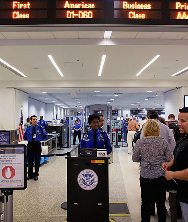 Passengers wait to clear security next to the newly opened TSA PreCheck lane at Miami International Airport on Oct. 4, 2011