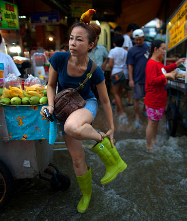 Patarawan fixes her boots as her pet parrot, Sim sits on her head as she goes shopping for dinner at a busy flooded market near the Chao Phraya river Oct. 27, 2011 in Bangkok