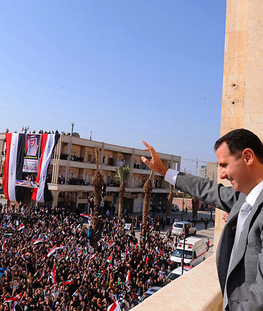 Syrian President Bashar Assad, right, waves to his supporters after he attended the prayer of Eid Al Adha, at the al-Nour Mosque in the northern town of Raqqa, Syria, on Nov. 6, 2011