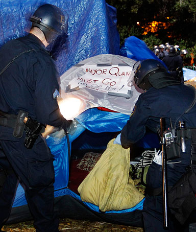 Police break up an encampment with a sign about Oakland Mayor Jean Quan for a Occupy Wall Street demonstration in Oakland, Calif., Monday, Nov. 14, 2011