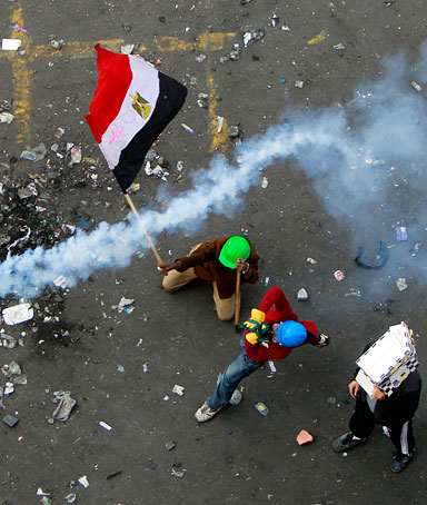A protester throws a tear gas canister, which was earlier thrown by riot police, as another protester waves the Egyptian flag at Tahrir Square in Cairo November 21, 2011