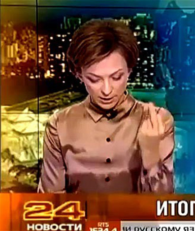 Tatyana Limanova raising her left arm and brandishing her middle finger just after she had referenced the US president's name during a news broadcast