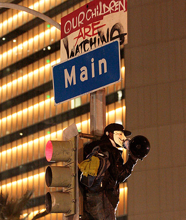 A protester yells from a light pole at the Occupy LA camp in Los Angeles on Monday, Nov. 28, 2011.