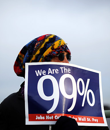 An Occupy DC demonstrator displays a placard as they protest on the Key Bridge in Washington, DC, on November 17, 2011, during a day of protests in a show of force by the Occupy Wall Street movement.
