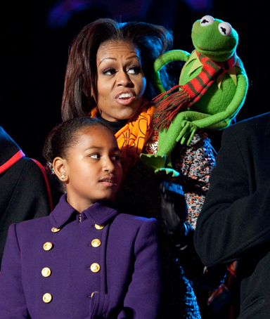 U.S. first lady Michelle Obama sings a Christmas carol with her daughters Malia (L) and Sasha and Kermit the Frog during the lighting of the National Christmas Tree in Washington December 1, 2011