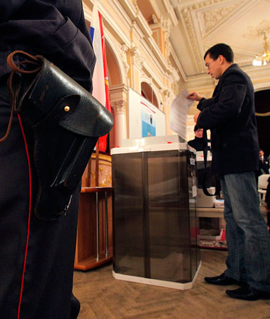 A police officer guards a polling station as a man casts his ballot during parliamentary election in St. Petersburg, Russia, Sunday, Dec. 4, 2011