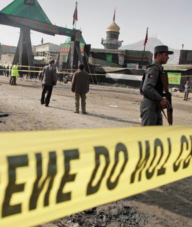 An Afghan police officer stands guard at the scene of a suicide attack in Kabul, Afghanistan, Tuesday, Dec. 6, 2011