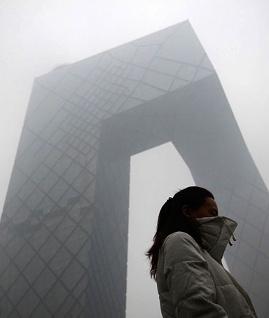 A woman walks past the new China Central Television (CCTV) building amid heavy fog in Beijing, December 5, 2011