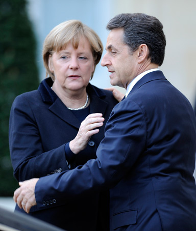 French President Nicolas Sarkozy says goodbye to German Chancellor Angela Merkel as she leaves after their meeting at the Elysee palace on December 5, 2011 in Paris