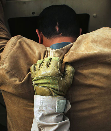 An Iraqi man is held against a Humvee by a US Marine after being searched during snap vehicle checks on February 8, 2006 in Ramadi, Iraq
