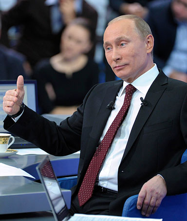 Russian PM Vladimir Putin gestures during a televised questions and answers session in Moscow, December 15, 2011