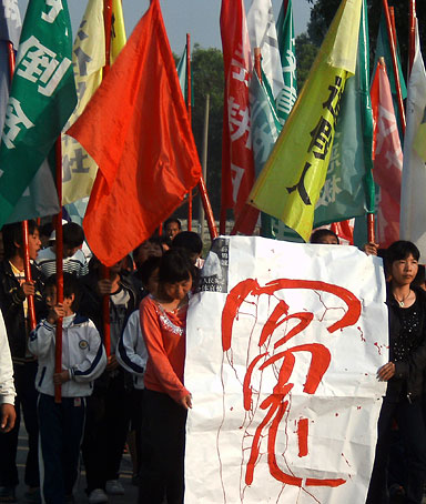 In this photo taken on Thursday, Dec. 15, 2011, villagers hold a poster with a Chinese word for