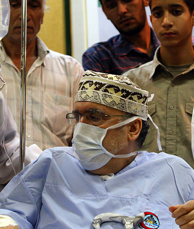 Lockerbie bomber Abdelbaset Ali Mohmet al-Megrahi speaks to a doctor as he wears a medical and sits on a wheelchair during a meeting with an African delegation at a hospital in Tripoli on September 9, 2009