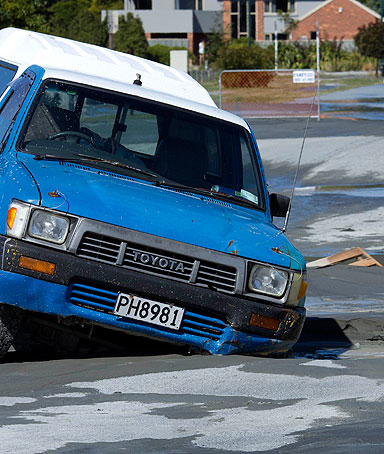 A car is trapped in the middle of the road in a sink hole caused by liquefaction in the Christchurch suburb of Parklands after an earthquake struck December 23, 2011