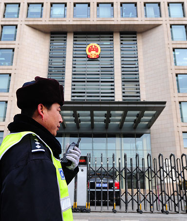 A policeman speaks into his walkie talkie while on patrol outside the off-limits courthouse where a Beijing court upheld on appeal the 11-year jail term for leading Chinese dissident Liu Xiaobo