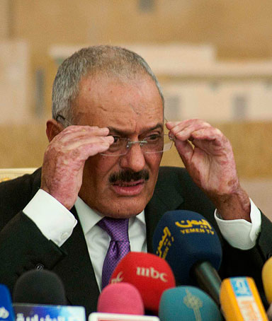 Yemen's outgoing President Ali Abdullah Saleh adjusts his spectacles during a news conference in Sanaa December 24, 2011