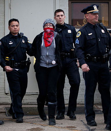 Danielle Ryun, a protestor affiliated with the Occupy Wall Street movement, is arrested by members of the Des Moines police department for blocking an entrance to the Iowa Democratic Party headquarters on December 29, 2011 in Des Moines, Iowa.