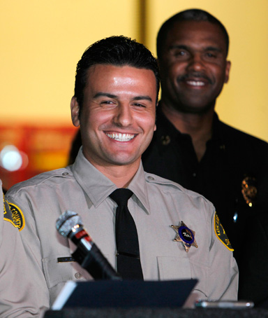 Los Angeles County Reserve Deputy Sheriff Shervin Lalezary (right) smiles as he is introduced by Sheriff Lee Baca (left) during a news conference in Los Angeles January 2, 2012