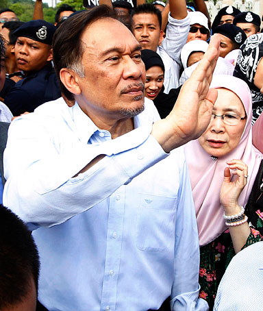 Malaysian opposition leader Anwar Ibrahim waves to his supporters after coming out from the High Court where he heard the verdict of his sodomy trial in Kuala Lumpur, Malaysia, Monday, Jan. 9, 2012