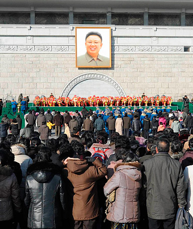 North Koreans line up to offer flowers at a portrait of the late leader Kim Jong-il in Pyongyang on the date marking Lunar New Year, January 23, 2012.