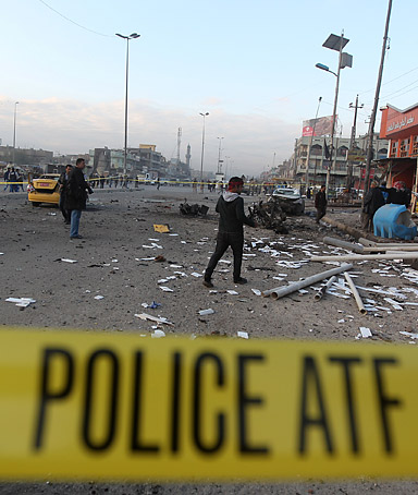 Iraqi security forces and civilians inspect the site of a blast after a bomb ripped through a group of workers in Sadr City in Baghdad on January 24, 2012.