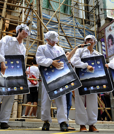 Participants dressed as Foxconn workers take part in a protest against Taiwanese technology giant Foxconn, which manufactures Apple products in mainland China, outside an Apple retail outlet in Hong Kong on May 7, 2011.